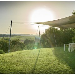 Image showing the garden of a modernised historic property in tuscany with shaded dining area on lawn with rolling hills view and sun set