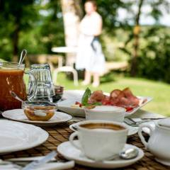 image showing coffee cup with capuccino jam and other items served at breakfast in a garden in tuscany with a woman out of focus in the back ground