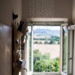 Image showing the shower in a modernised historic tuscan country house villa showing the view from behind a stream of water from the shower showing the rolling hills scenery from the bathroom window of the siena room
