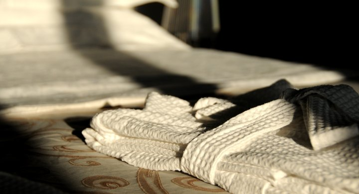 Image of a bed with grey Frette linen and white nido d'api beehive folded bath robe