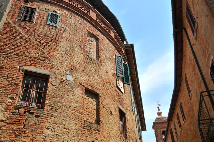 Image showing red brick built tuscan hill town in the province of siena with wall detailing and shuttered windows