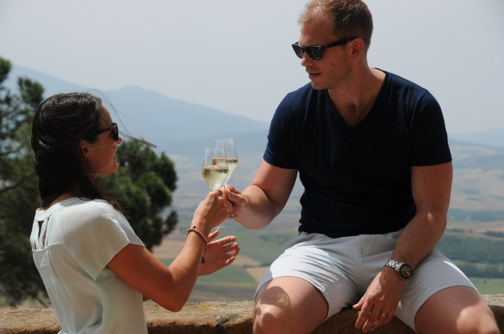 image showing two people together at sitting on the wall by the view taking glass of prosecco at bar il cassello Pienza