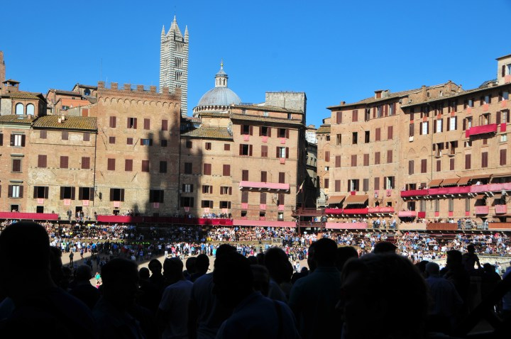 image of the Piazza del campo in siena, showing the opposite side to the torre di mangia with the shadow of the tower cast on the buildings and crowds of people in the foreground in shadow and the racetrack ready for the race visible