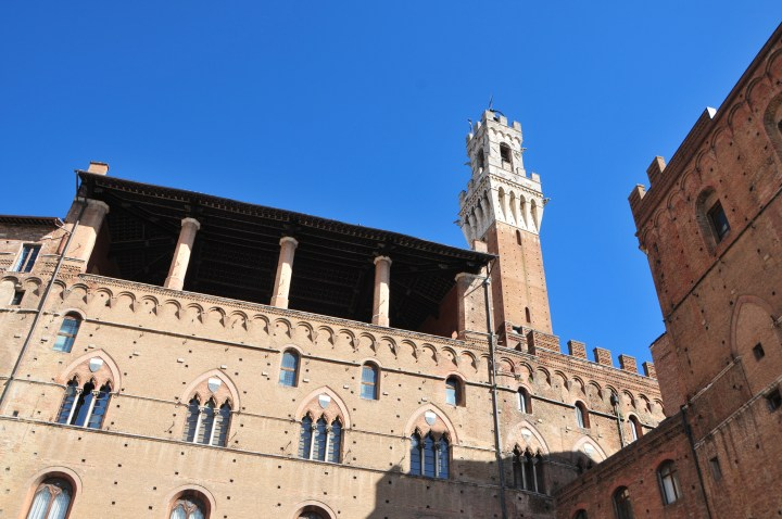 detail of architecture in the Piazza del mercato in Siena showing loggia with the high tower torre di mangia in the main square behind