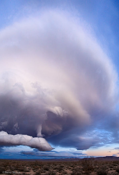 A wild lenticular cloud formation slowly grows and moves across the Northern Mojave Desert.