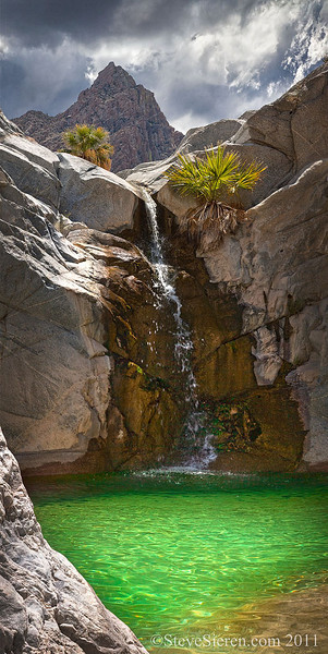 Summer monsoon clouds over an emerald pool and waterfall in Baja California, Mexico