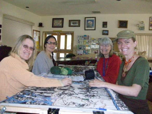 Deborah Love, Geli Duarte, Mary Moore, artistic director, and Skyler Meyers, enjoy stitching on Tapestry No. 5, the history of gold mining on the Ridge from 1970 to present, most Wednesday afternoons at the North San Juan Senior Center on Route 49, North San Juan.