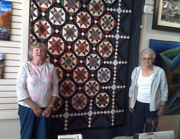 Earlene Folsom and Karen Laux near the Mt Star Quilters Raffle Quilt for 2016