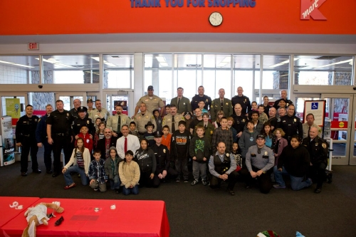 The whole group of officers, deputies, chiefs and happy kids.