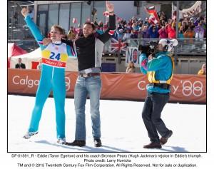 Eddie (Taron Egerton) and his coach Bronson Peary (Hugh Jackman) rejoice in Eddie's triumph.