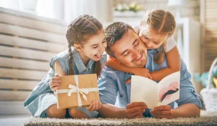 pai e duas filhas comemorando o dia dos pais com presentes