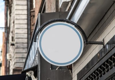 Generic white round sign mounted to the wall over a shop entrance. Insert your own text.