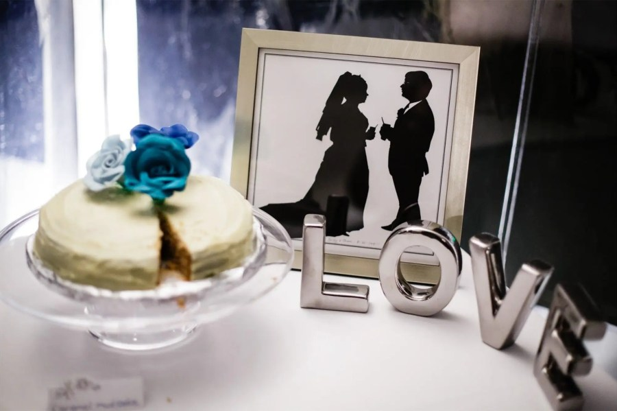 "Silhouettes of a bride and groom next to a cake and the work ""LOVE"": wedding memories"