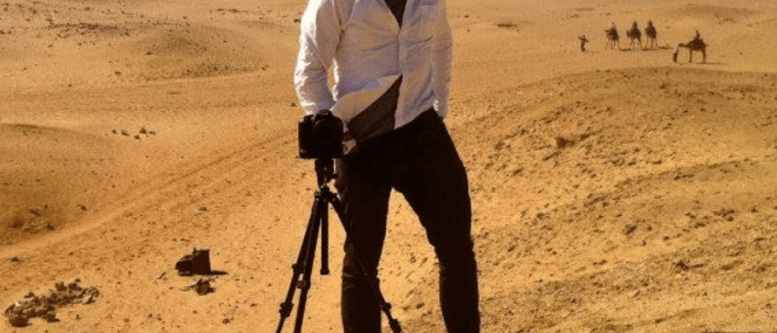 "Self-portrait of Casey Neistat standing in front of a camera on a tripod atop a sand dune in the desert with camels in the background. Apparently taken during filming ""Make It Count"" for Nike."