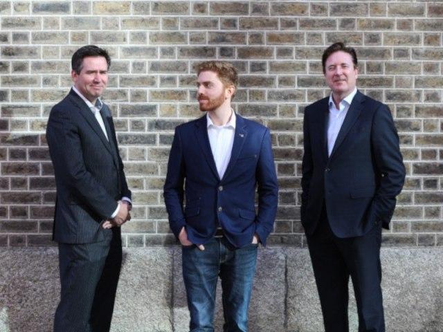 Trois hommes en costume debout contre un mur.