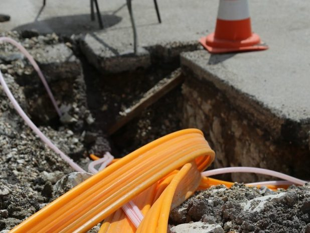 Some roadworks for the installation of fibre broadband, featuring large fibre cable and a traffic cone.