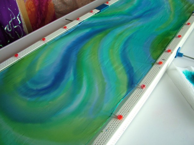 Painting the base layer of blues and greens on the silk scarf