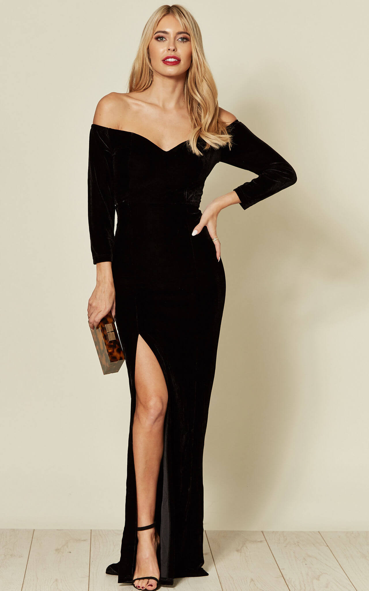 Model wears off the shoulder black velvet maxi dress with side slit and barely there heels