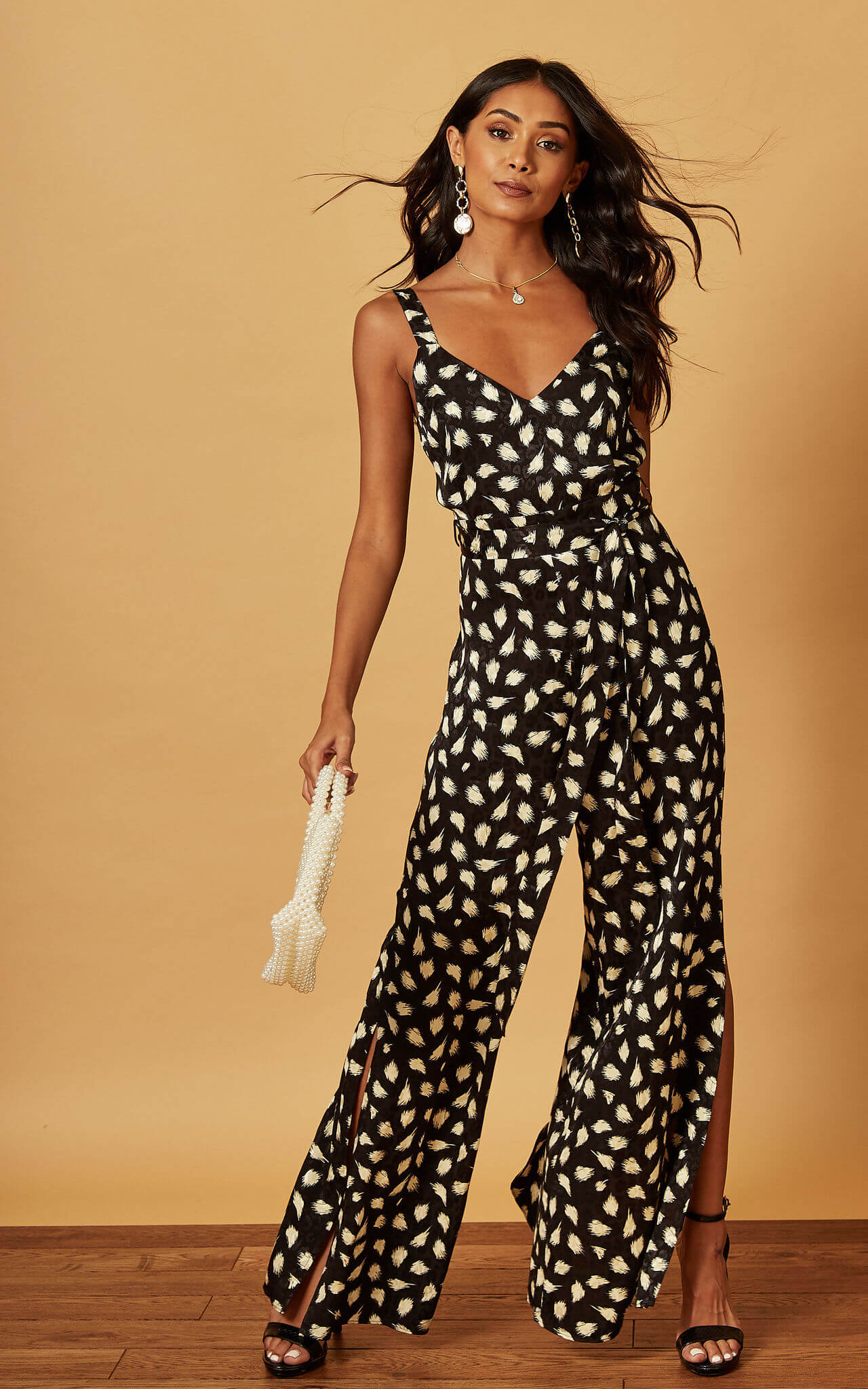 Model wears a abstract animal print strappy jumpsuit with black barely there heels and pearl bag