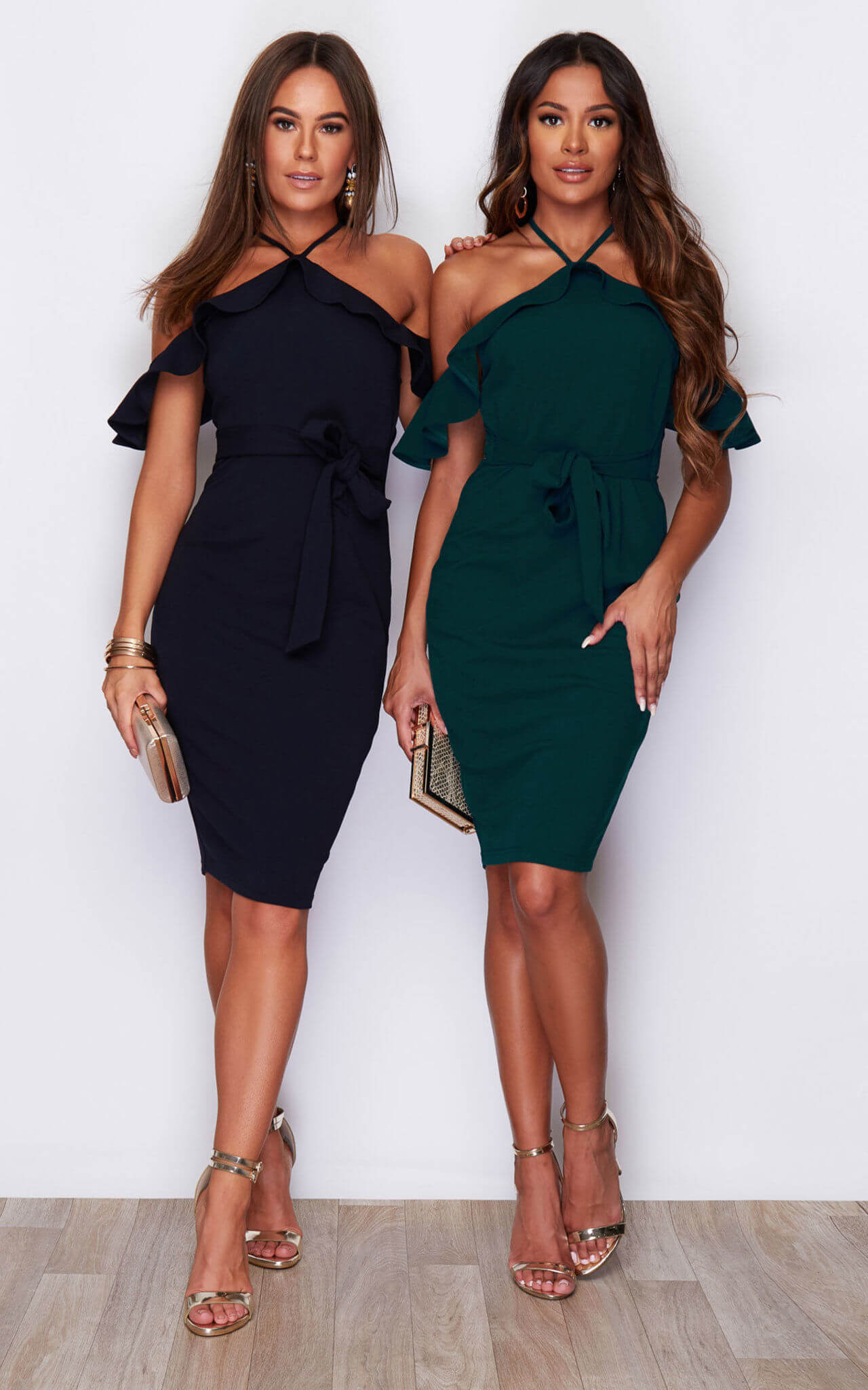 Two models wear an off the shoulder dress in navy and green