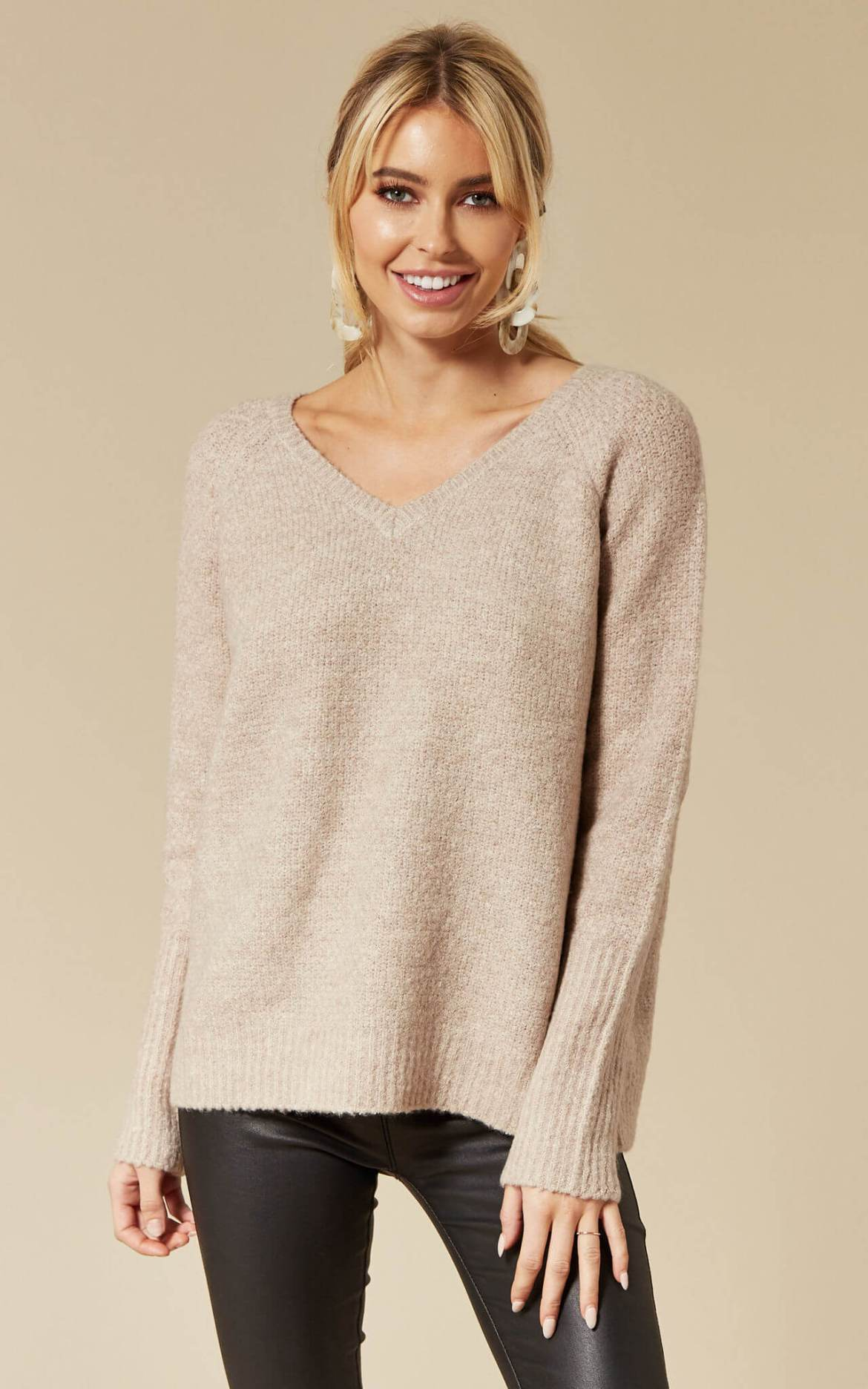 Model wears a natural coloured jumper with a v neckline