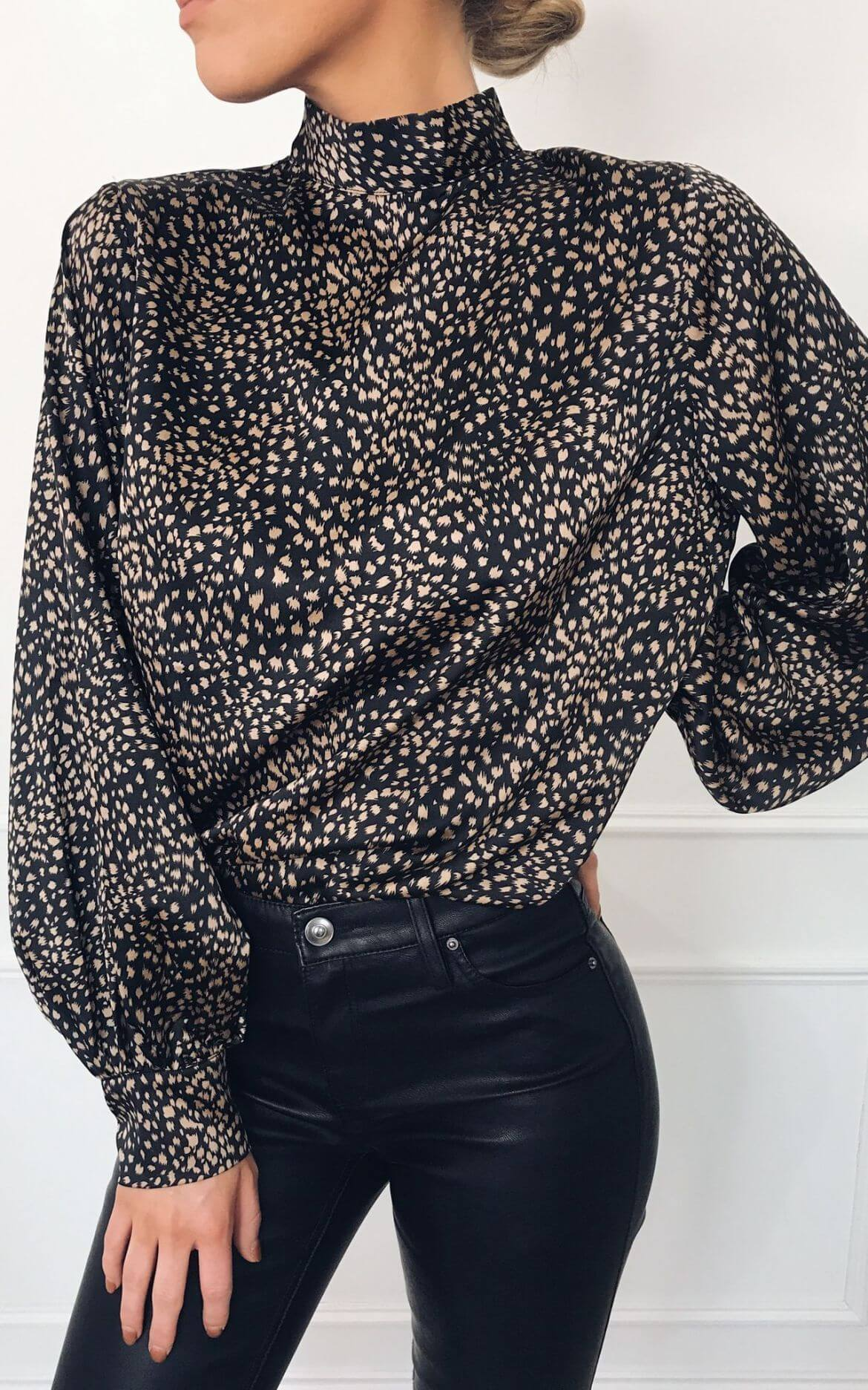 Model wears high neck animal print blouse with black jeans