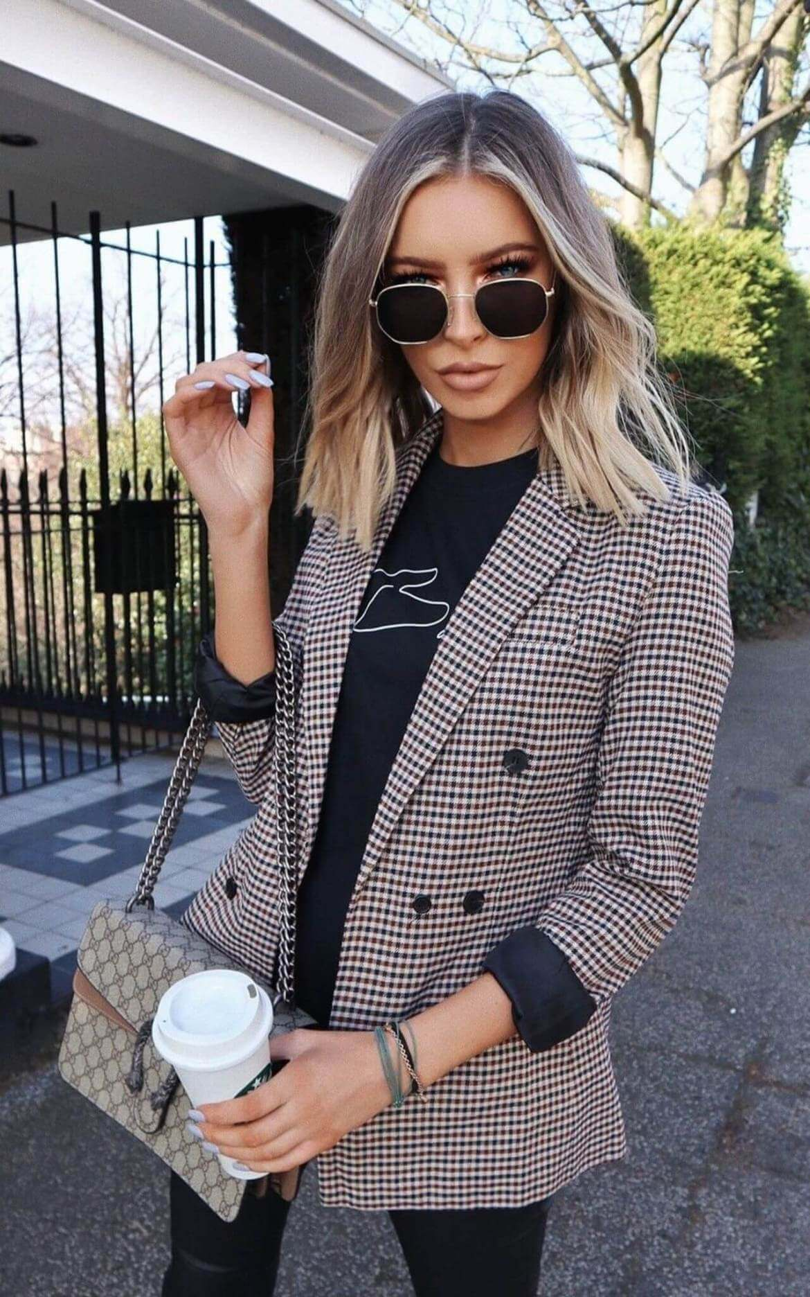 model wears check blazer and black t-shirt holding a coffee cup