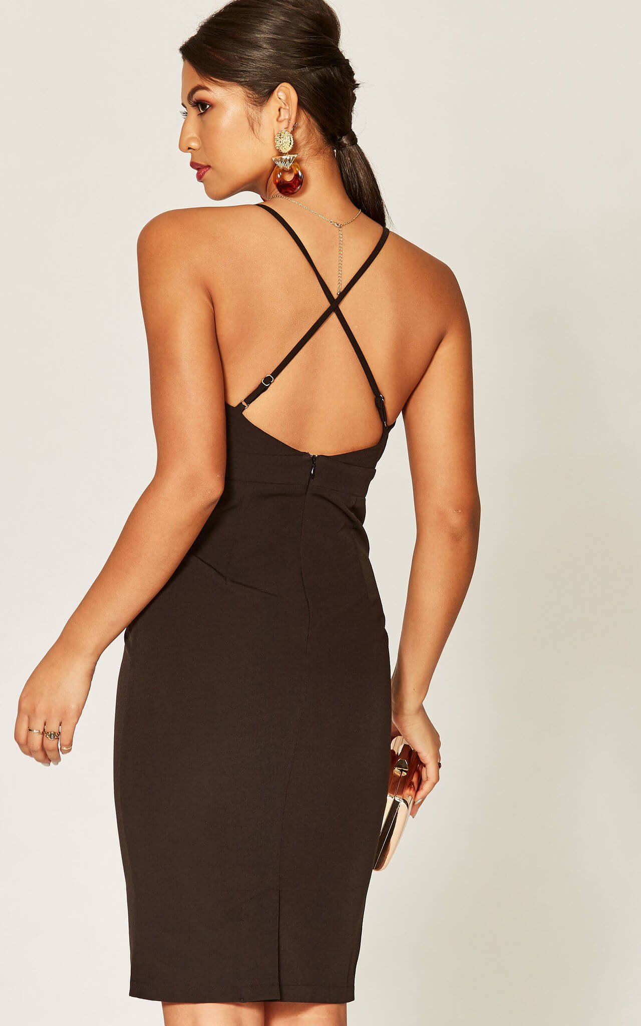Model has her back to the camera in a black dress with cross back straps