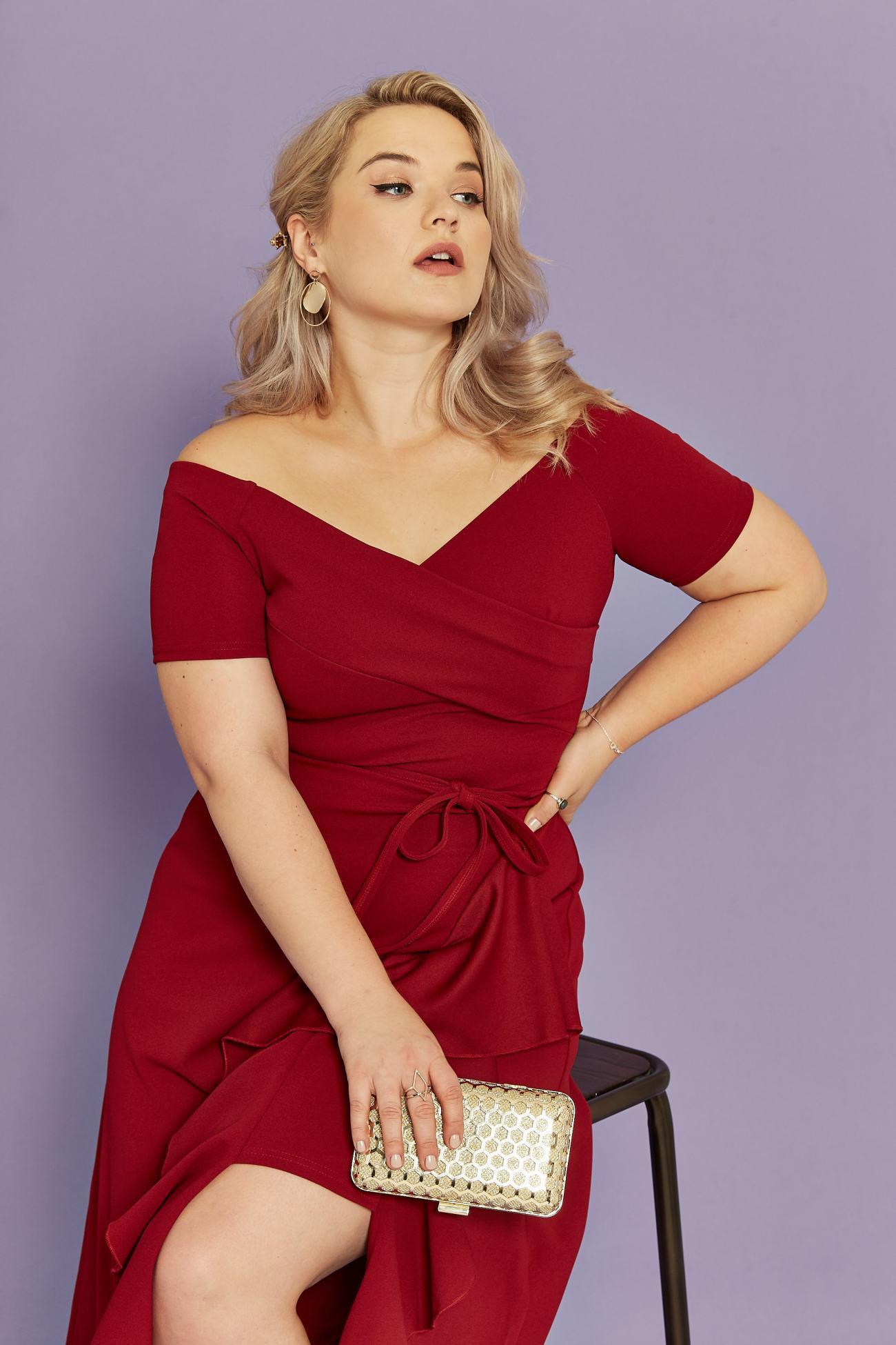 Model wears a bardot midi dress in burgundy in front of purple background