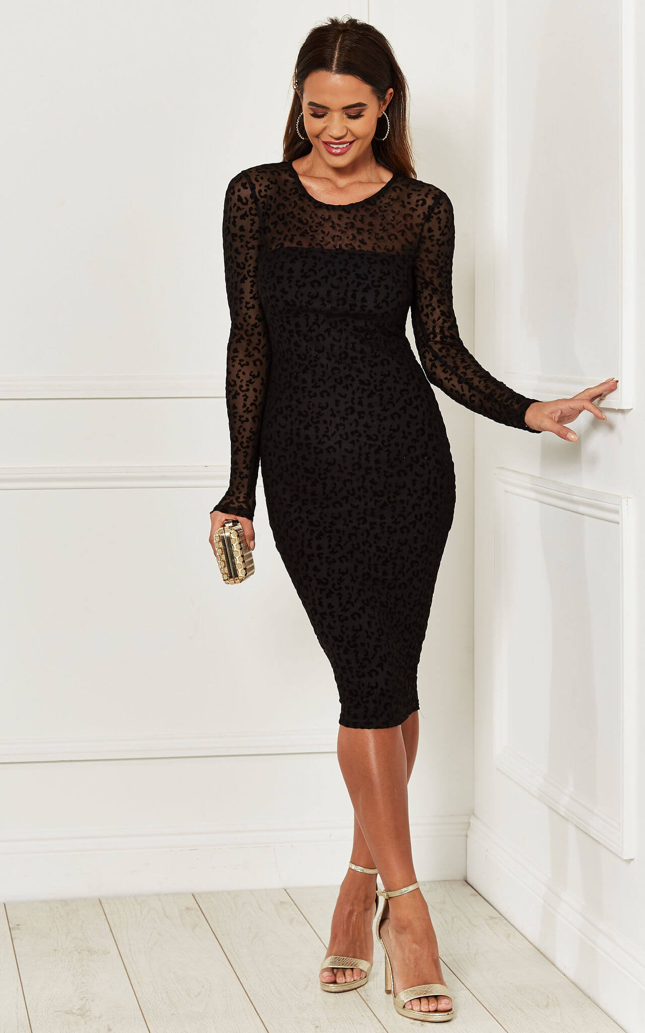 Model wears the black velvet bodycon burnout dress with nude heels and clutch bag