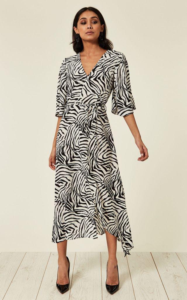 Model wears a wrap dress in zebra print with black heels.
