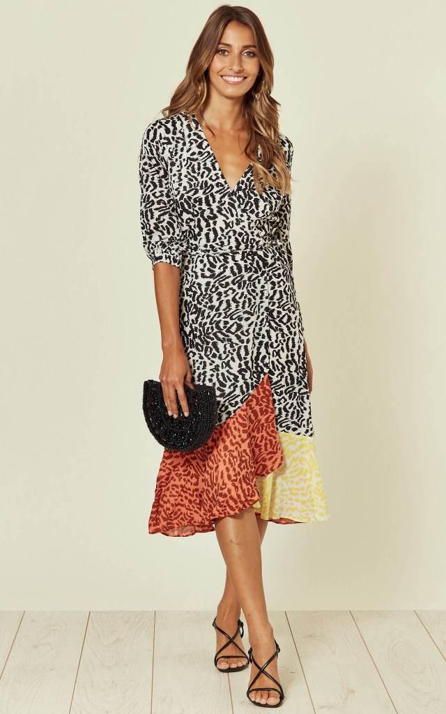 Model wears a wrap animal print dress with multicoloured hem with black heels