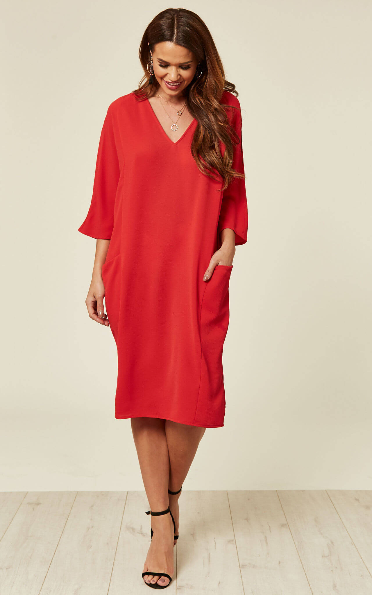 Model wears a red midi dress in relaxed fit with pockets