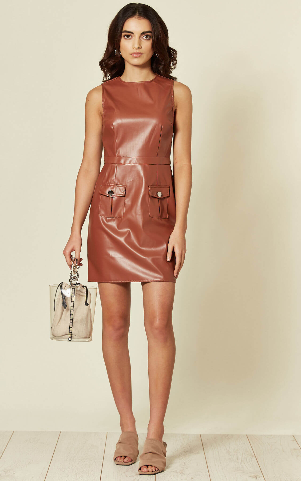 Model wears a faux leather brown bodycon dress with pockets and sleeveless