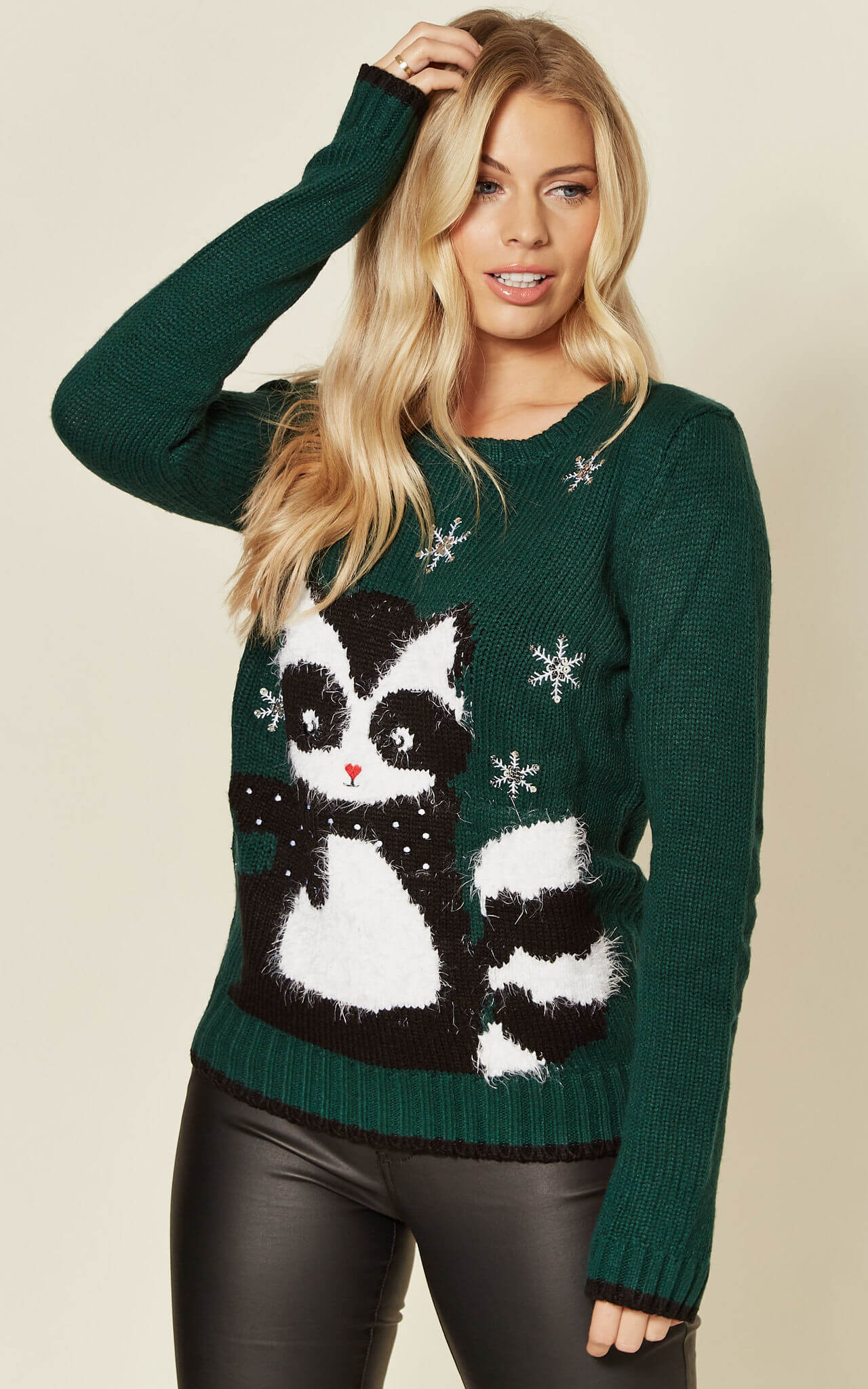 Model wears a green jumper with racoon and snowflake embroidery.