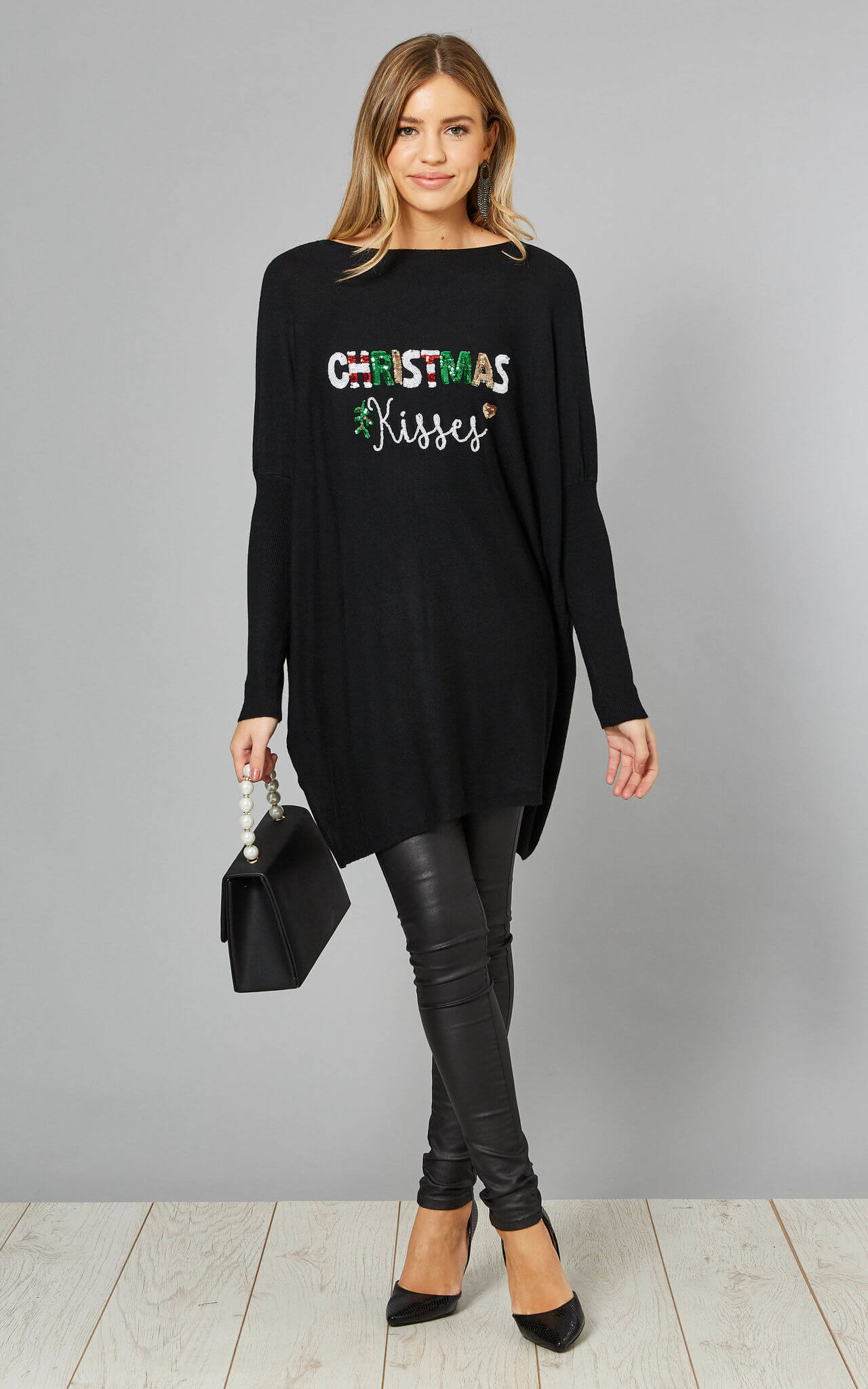 Model wears a black top with mutlicoloured sequin christmas kisses slogan