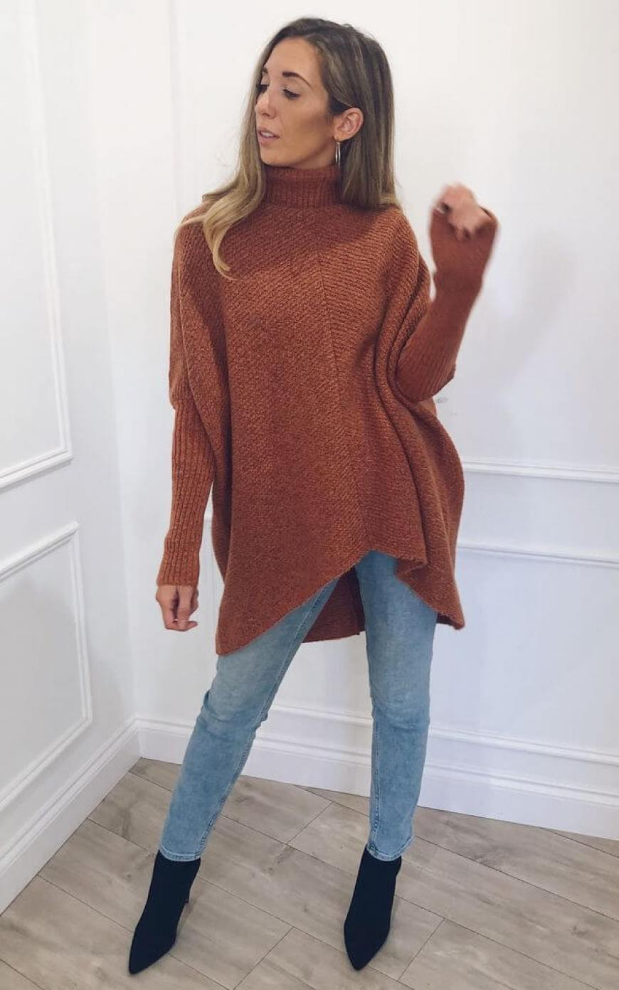 Model wears a brown roll neck jumper with blue jeans and boots