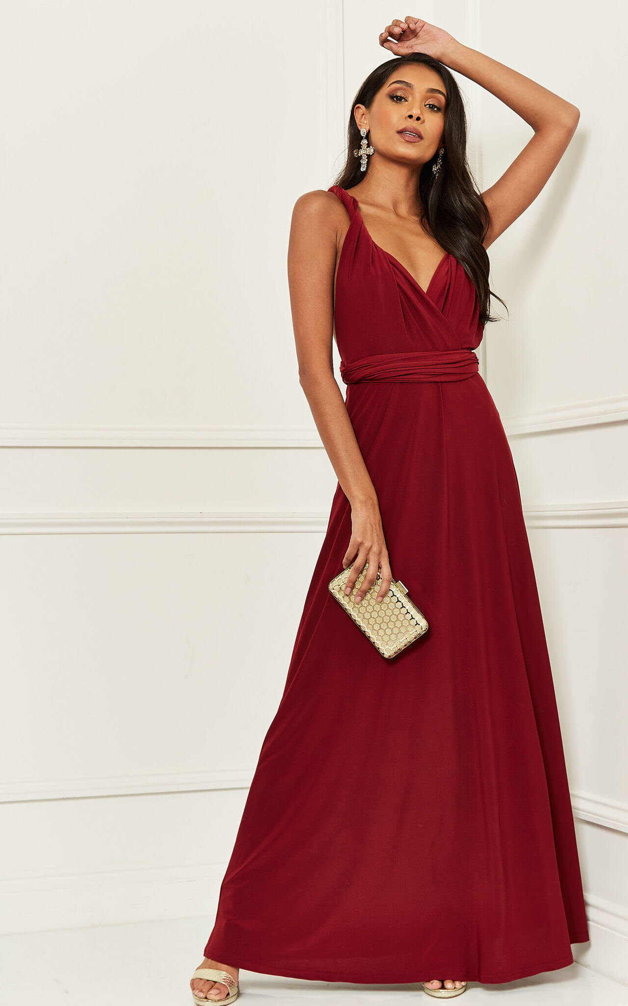 Model wears burgundy dress with multi-way straps and beaded clutch bag