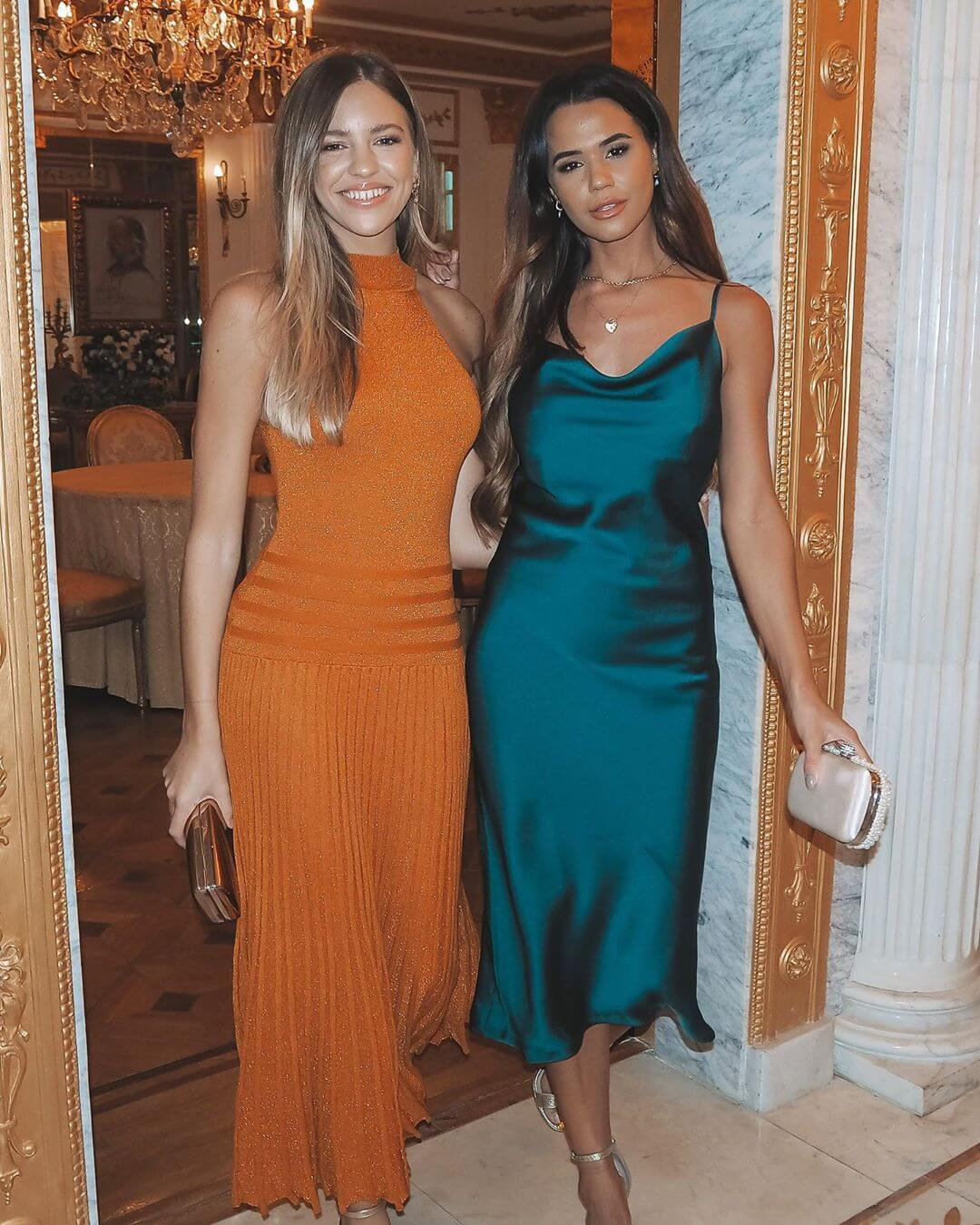 Two models in wear a green cowl neck satin cami midi dress and a high neck pleated metallic midi dress in a hotel room