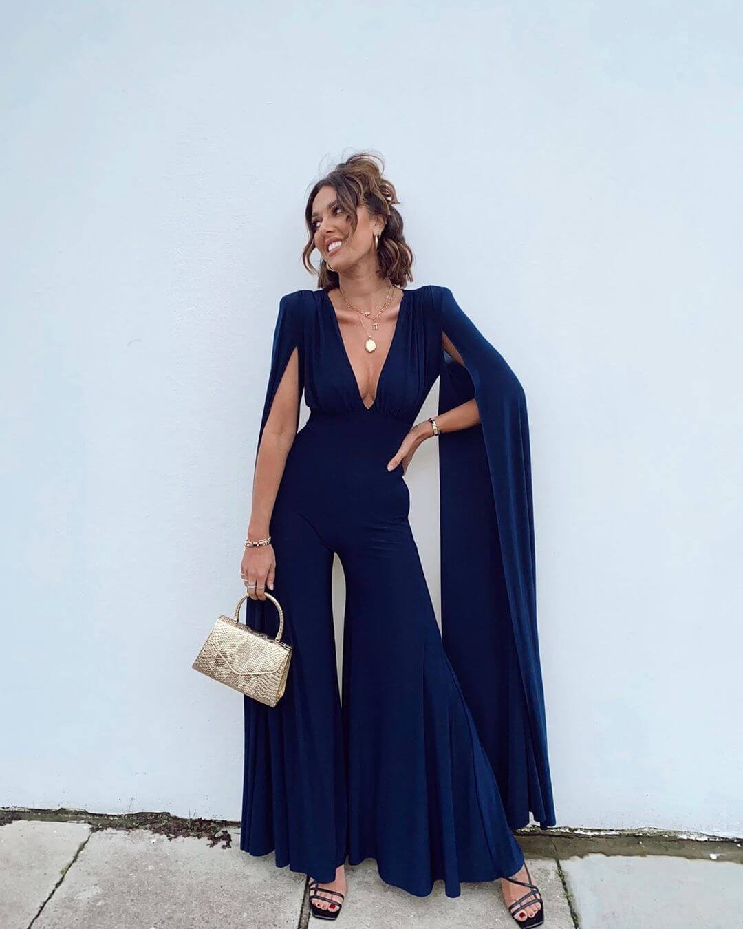 Model wears a navy plunge jumpsuit with cape details with a gold bag and nude shoes
