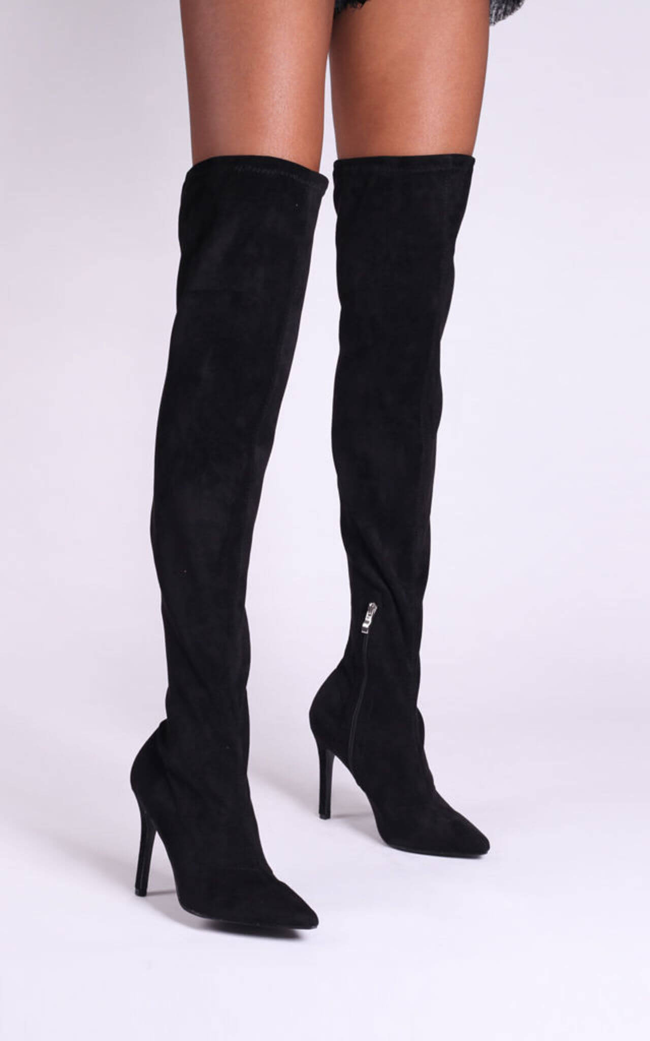 Model wears boots with pointed toe and stiletto heel in black