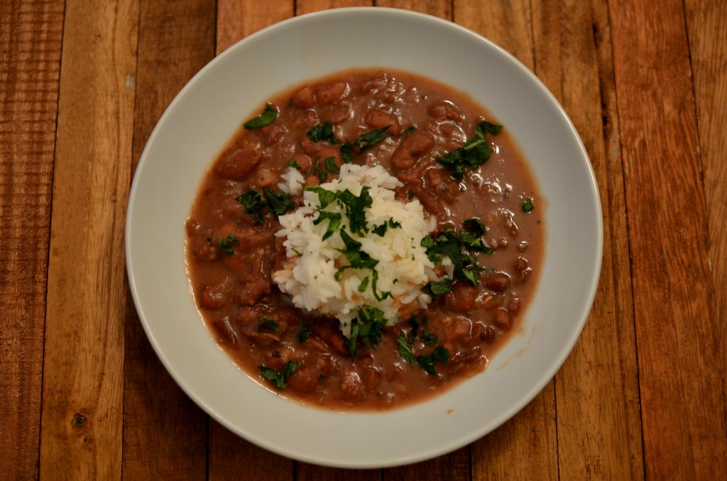 Red beans served with long grain white rice and garnished with parsely.