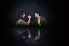 Dark view of Katherine and Sean arm wrestling, with their reflection in the table below