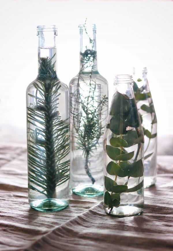 Decorare con le bottiglie di vetro, l'acqua e il verde.