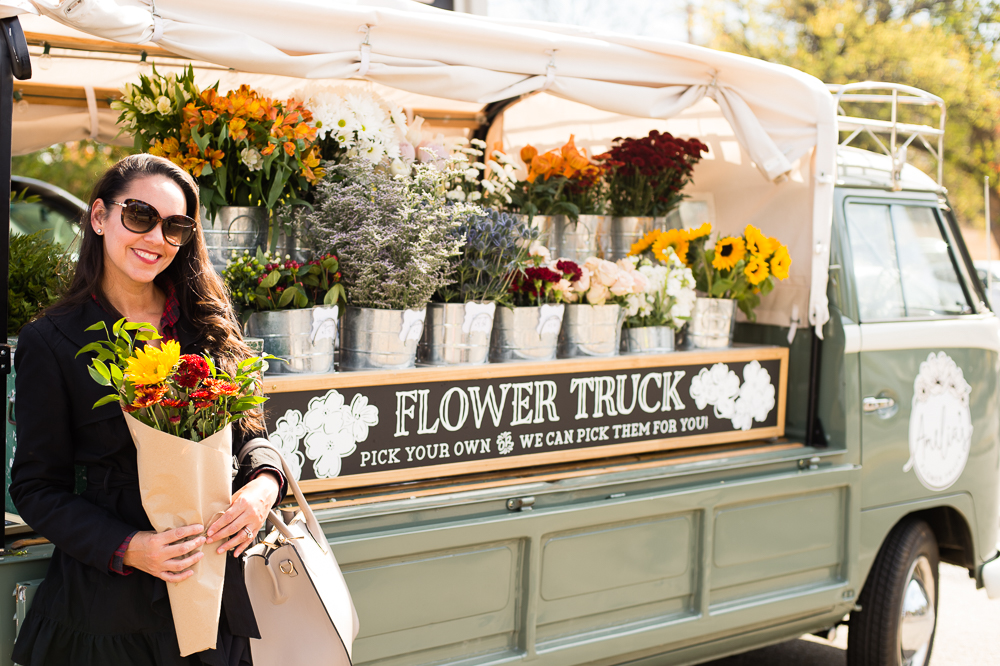 ali in front of amelia's flower truck at white's merchantile in Nashville Tennesse holding a bundle of flowers she just purchased