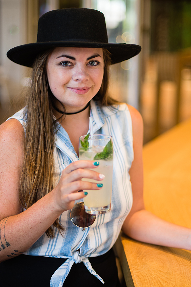 Brooke wearing a black hat having a lemonade at forthright cafe with pretty lights in the back