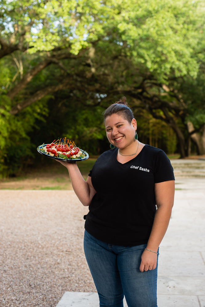 Sasha of Gregorios Catering with Caprese skewers in front of oak tree arch that is out of focus