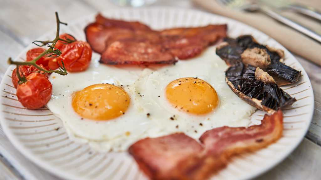 Low Carb High Fat Breakfast Meal. 2 Fried Eggs, 5 small vine tomatoes, Sliced Mushrooms. 3 strips Bacon. On wooden table. Cutlery visible to side.