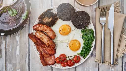 Low Carb High Fat Breakfast Meal. 2 Fried Eggs, 2 sausages, spinach, 5 small vine tomatoes, 2 slices black pudding, Sliced Mushrooms. 3 strips Bacon. On wooden table. Cutlery visible to side.
