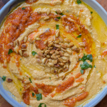 Bowl of hummus with pine nuts, olive oil and parsley